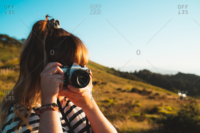 Blonde girl taking a photograph with a vintage film camera