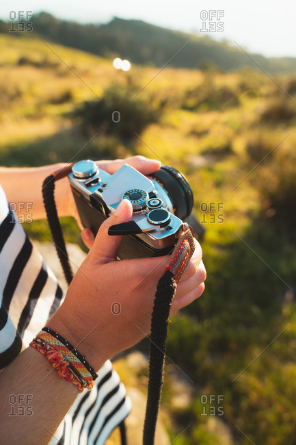 Female hands holding an old vintage film camera outdoors
