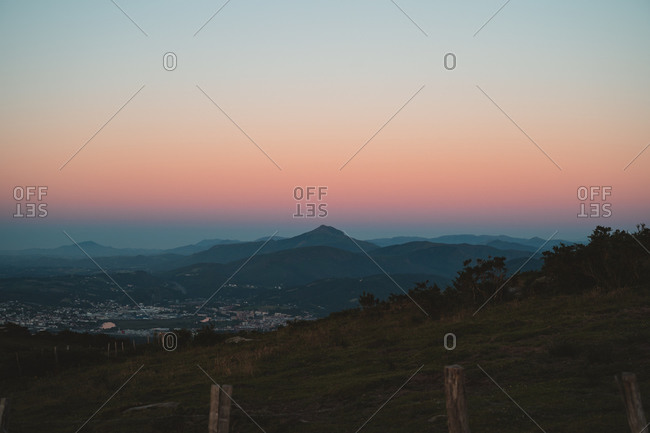 Gradient of cold and warm tones on the sky after sunset and layers of mountains