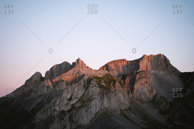 Rocky mountain range peaks glowing during sunrise in Pyrenees