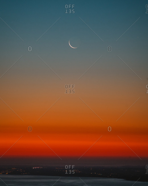 Gradient sky with a super thin crescent moon before sunrise