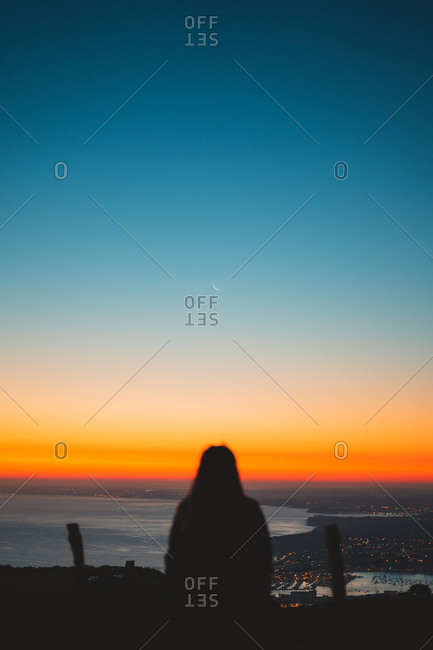 Blurry silhouette of a girl looking at the moon during a spectacular sunrise