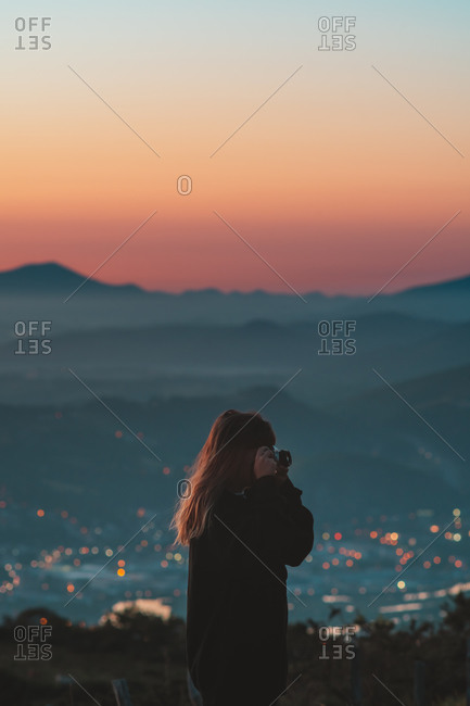 Young caucasian girl taking photos on a vintage film camera during sunrise in Jaizkibel, Basque Country
