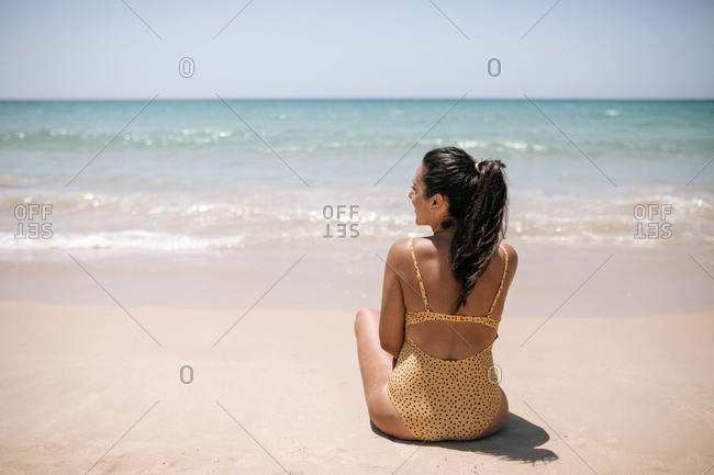 Young woman in yellow swimsuit sitting on the beach looking out to sea