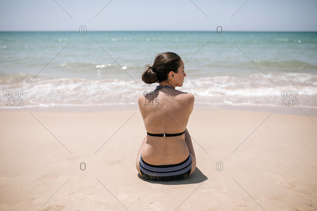Young woman in bikini sitting on the sand looking out to sea