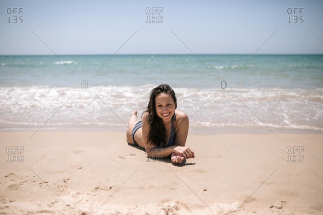 Young woman lying on the sand of a nice beach