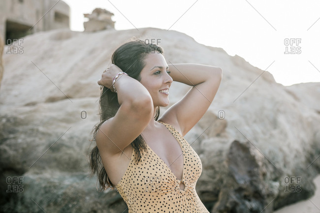 Portrait of young woman on a beach with rocky stones