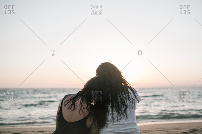 Two women hugging on the seashore watching the sunset