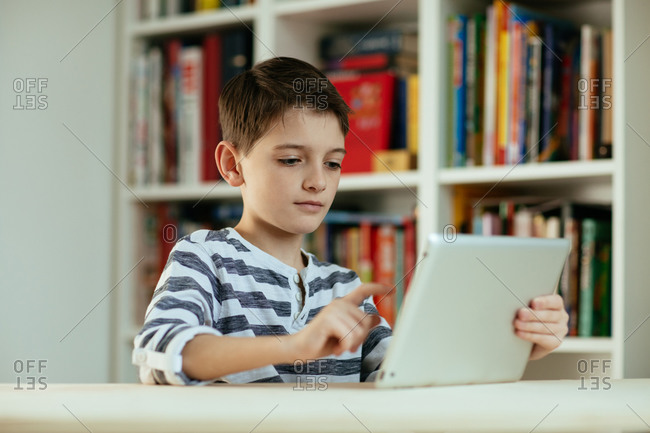 Serious boy using digital tablet at home. Portrait of boy using digital tablet and concentrating.