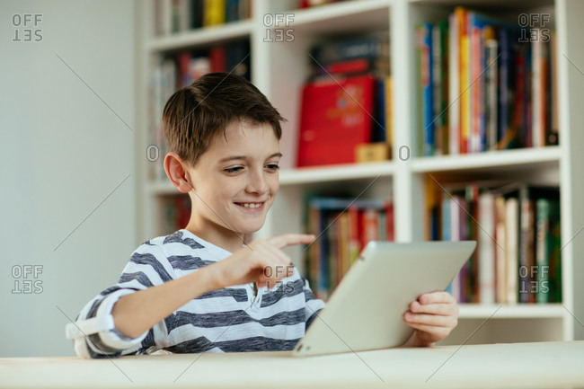 Young boy using digital tablet. Portrait of cheerful boy using digital tablet at home smiling.