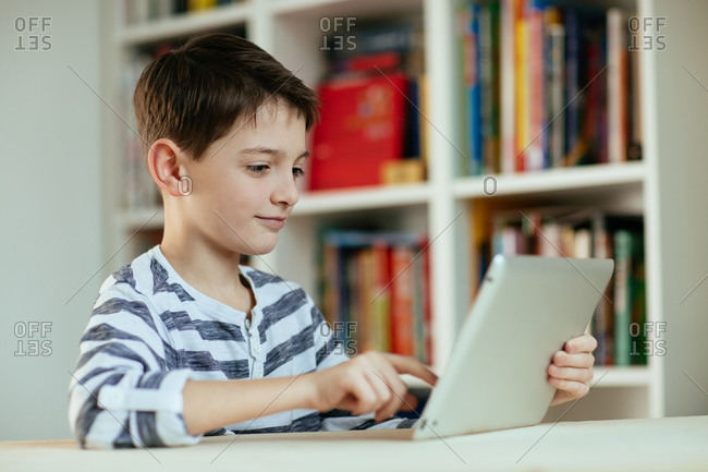Boy using digital tablet at home. Portrait of boy using digital tablet and concentrating.