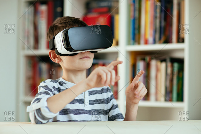 Young boy wearing VR headset. Head and shoulders of boy using Virtual Reality technology at home.