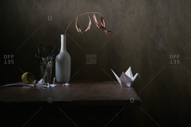 Paper crane and forced emigration. Still life.
