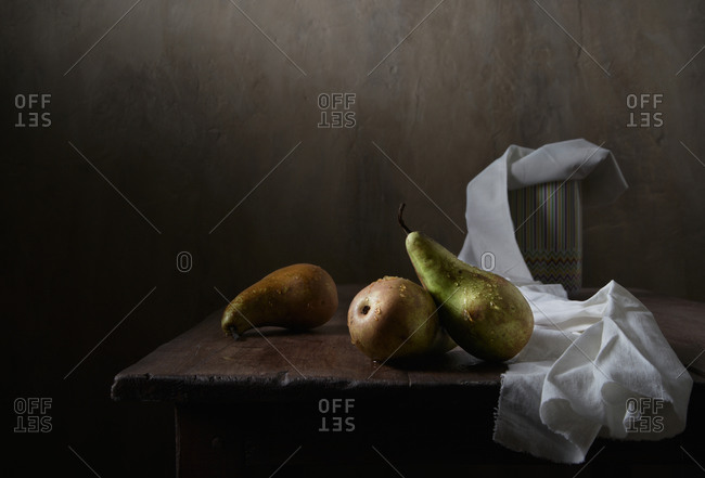 Green pears in drops of water. Still life in a low key