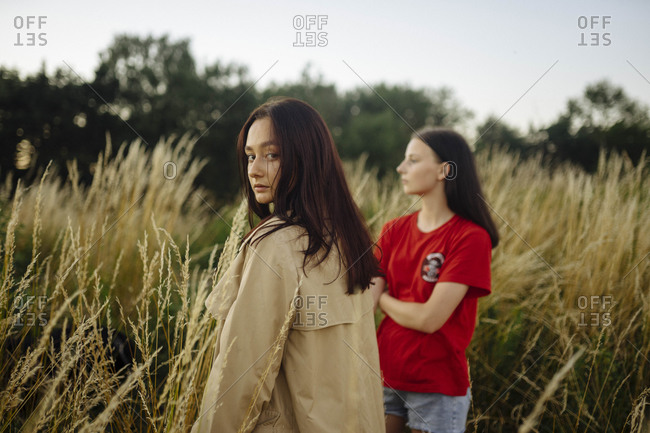 Two women standing in tall grass