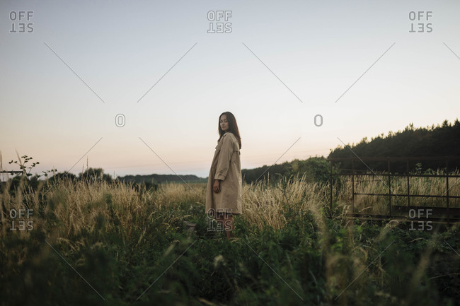 Woman in tall grass at sunset