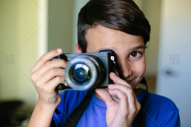 Portrait of a boy holding a camera up to his eye