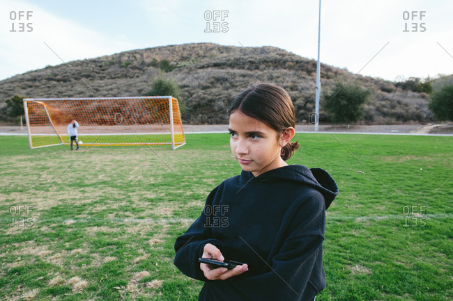 Tween girl holds her cellphone while looking off while at a park