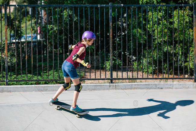 Teen skater girl skates at a skate park while wearing protective gear