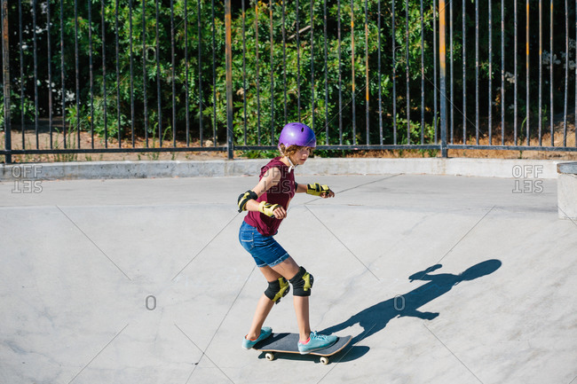 Teen girl in a purple helmet skateboards down a canyon at skate park