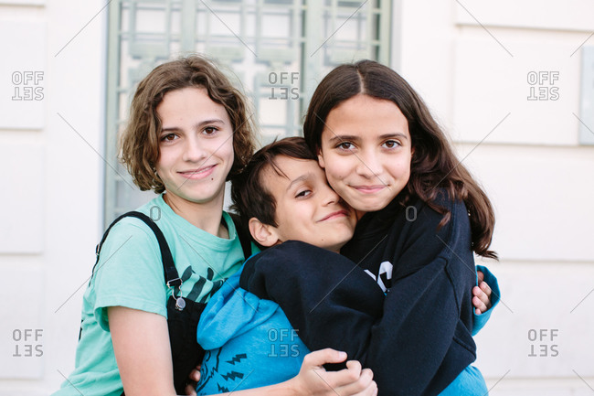 Young teen girls make a brother sandwich as they embrace