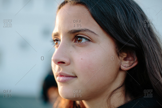 Close up profile of a twelve year old girl in half lit by the sun
