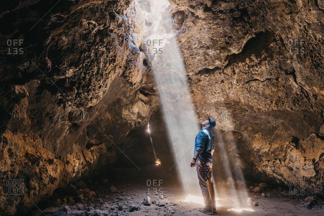 Man admires a light beam that cuts through the cave