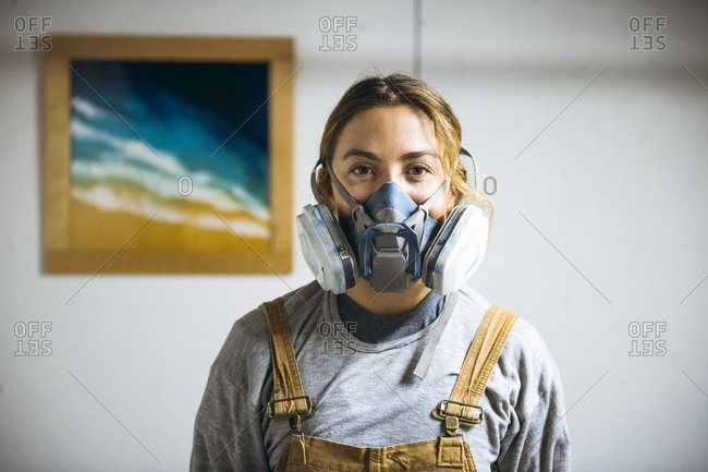Portrait of female resin artist in homemade art studio with respirator