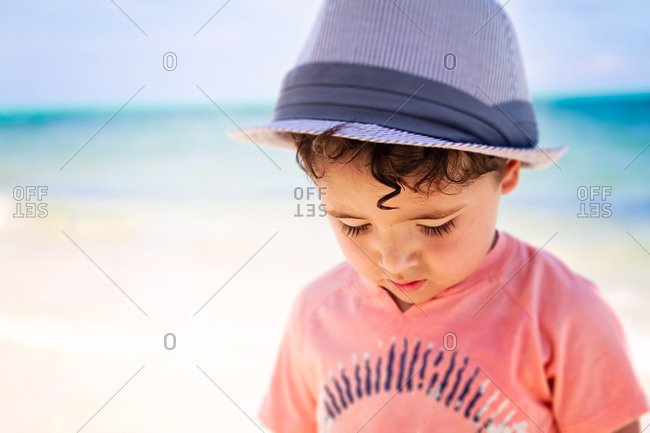 Little boy with curly hair walking a the beach in the Caribbean
