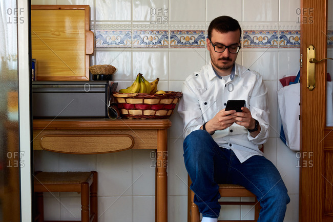 Young man looks at his phone sitting on a kitchen chair