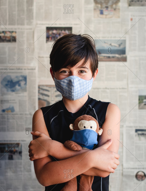 Young boy wearing mask holding toy monkey with newspaper backdrop.