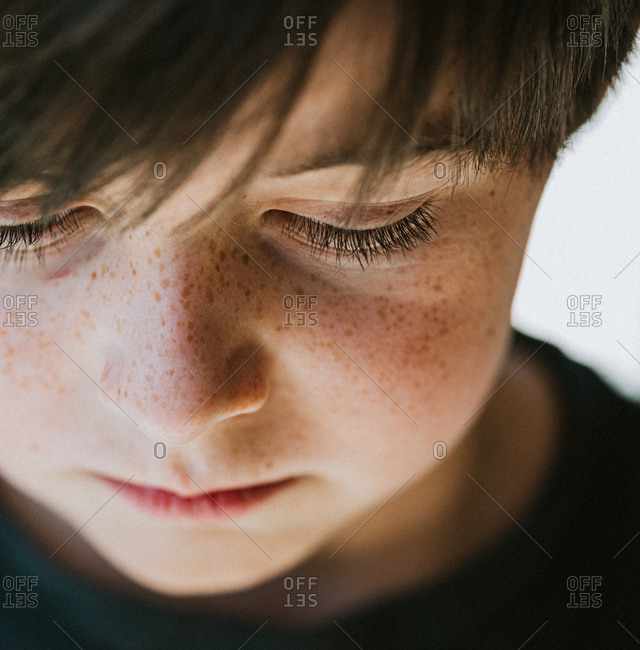 Close up of the face of a young boy with freckles looking downward.