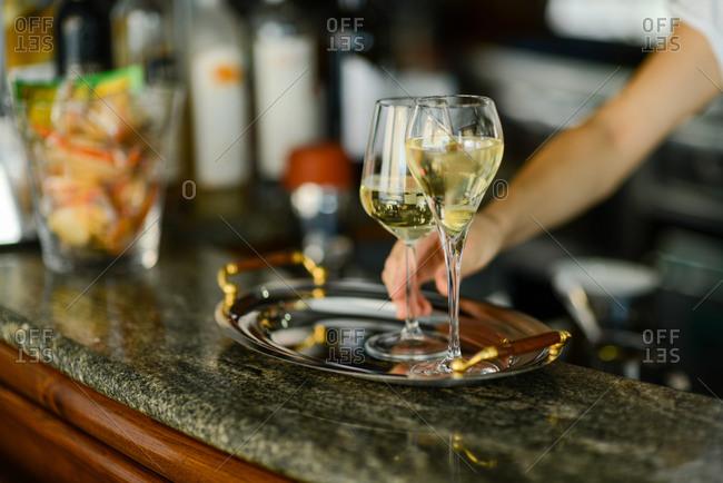 Hands of young adult caucasian female barista preparing white wine