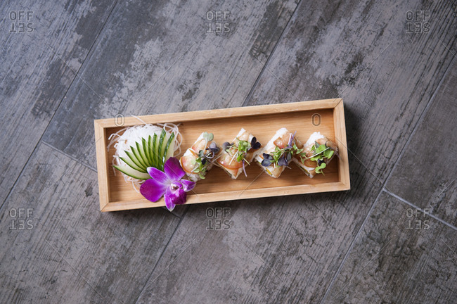 Sushi Roll on a wooden tray toped with micro greens