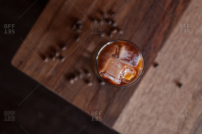 Tall Glass of cold brew iced coffee on a wooden coffee table