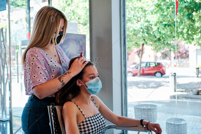 a hairdresser wearing a face mask making curls at the beauty saloon - coronavirus crisis concept