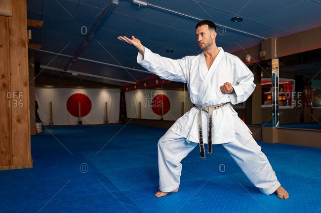 Karate man stand your ground on tatami doing 'Shuto Uchi'