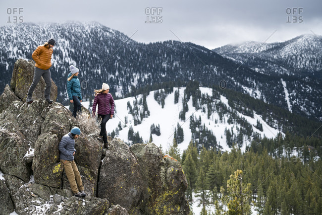 Group of friends hiking on boulders in winter