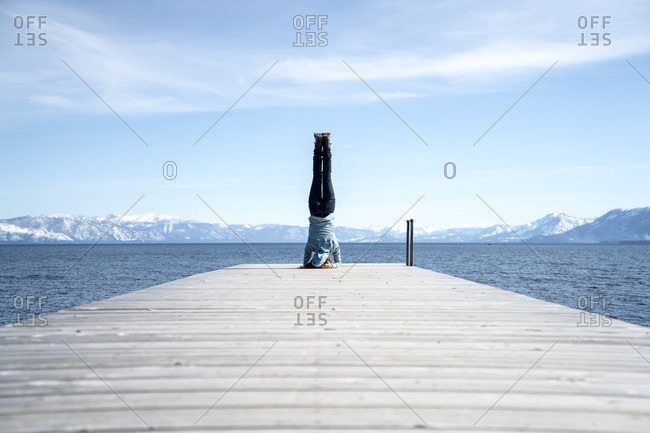 Woman does a headstand at the end of a pier in South Lake Tahoe, CA