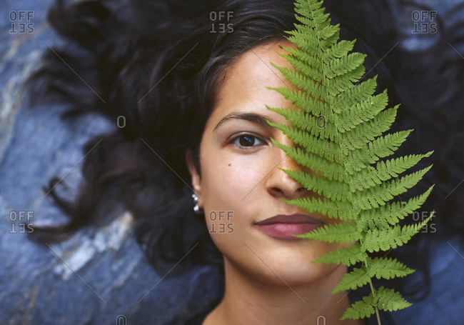 Woman with a fern on her face. She's lying on a rock and covers