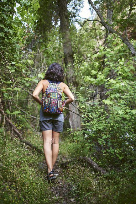 Young girl walking in the woods. She has a backpack on her back.