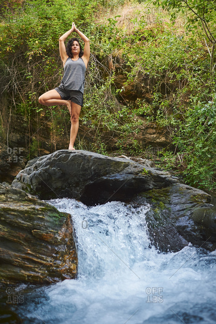 Young woman practicing yoga in a river. She's in the middle of nature.