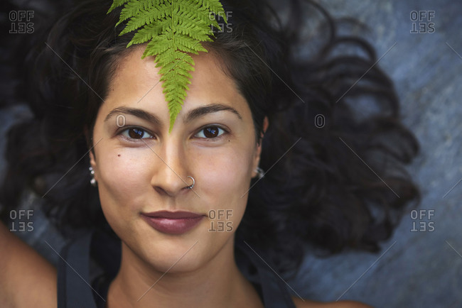 Woman with a fern on her face. She's lying on a rock and covers half her face with a fern leaf.