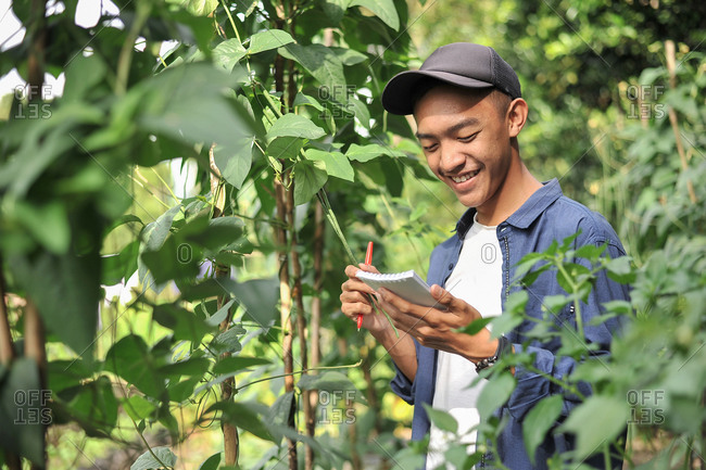 Portrait of smiling young Asian farmer man writing on the small notebook. Happy young Asian farmer at the garden