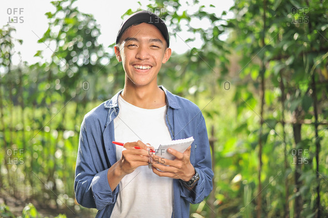 Happy of smiling young Asian farmer male holding the notebook on green garden