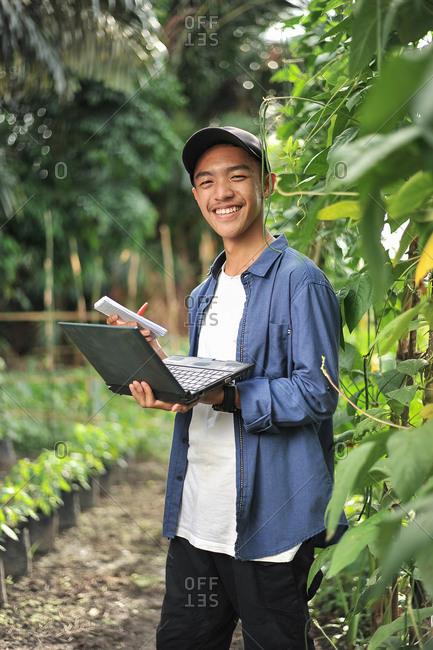 Young Asian farmer man holding laptop at the garden