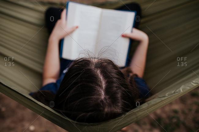 Center overhead frame of teen girl reading in hammock