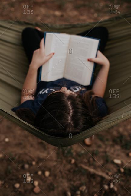 Vertical overhead of teen girl sitting in hammock reading