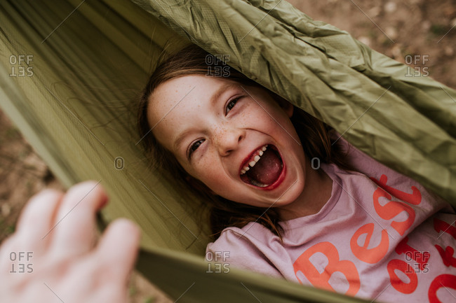 Overhead of silly girl laughing in hammock