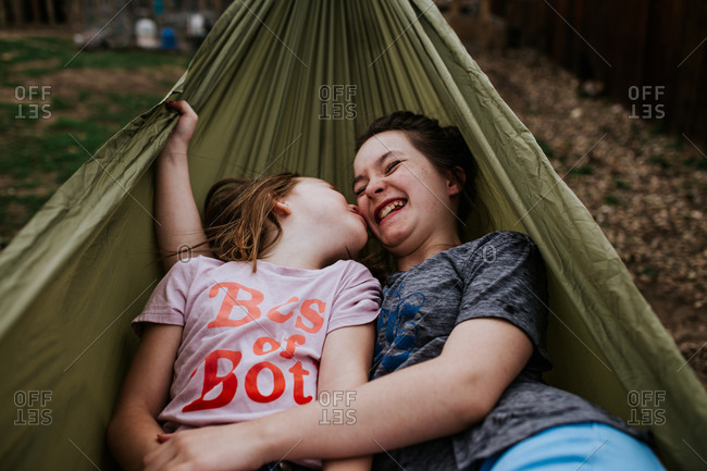 young girls goofing around in hammock outside